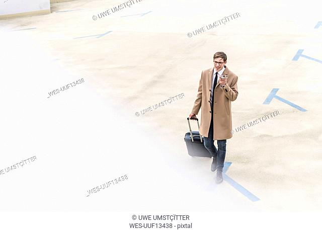 Businessman with rolling suitcase and smartphone walking at parking garage