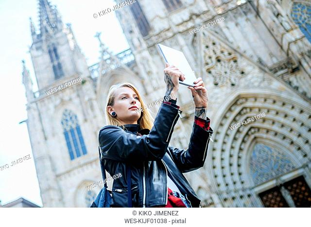 Spain, Barcelona, young woman taking picture with tablet in front of cathedral