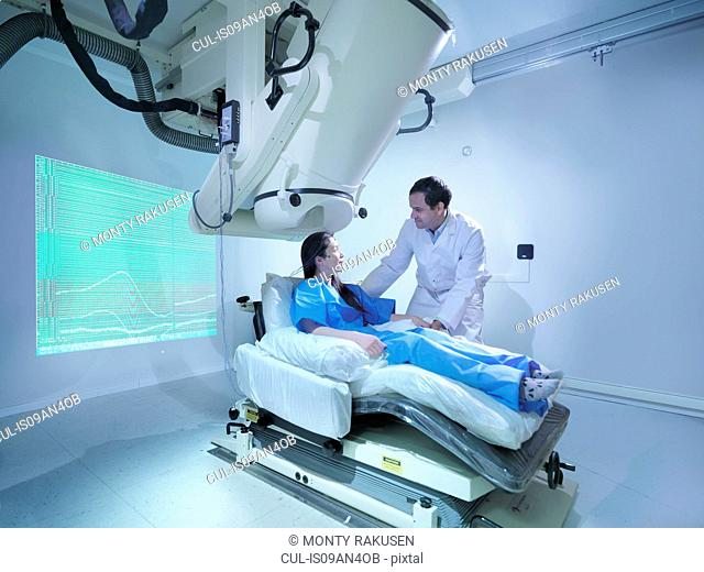 Doctor with patient using magnetoencephalography (MEG) scanner