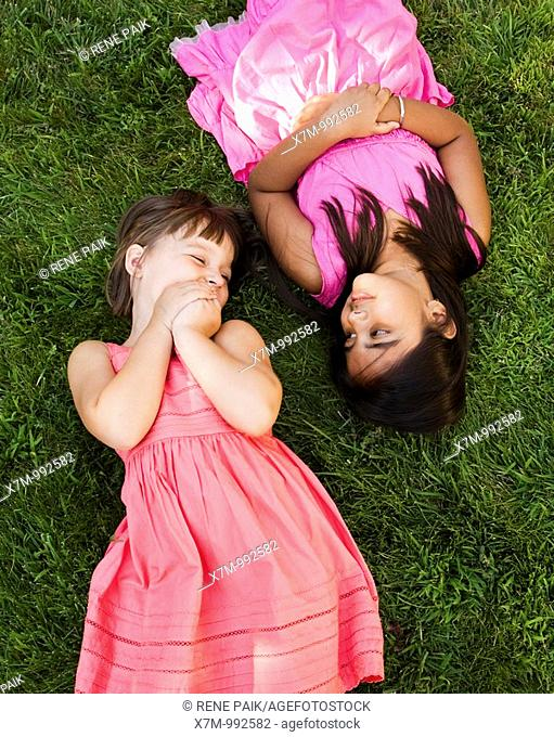 A little caucasian girl and an Asian Indian girl lay in the grass to relax and play