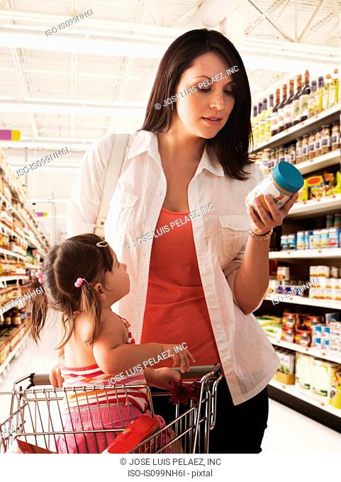 Mother reading label on baby food jar in supermarket