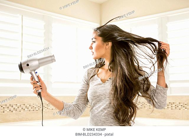 Mixed Race woman drying hair in bathroom