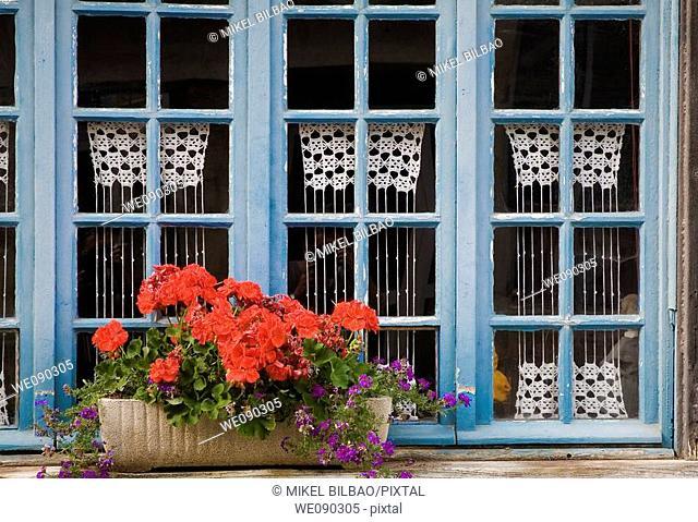 wooden window with flowers.Tréguier (Breton: Landreger) is a port town in the Côtes-d'Armor department in Bretagne in northwestern France