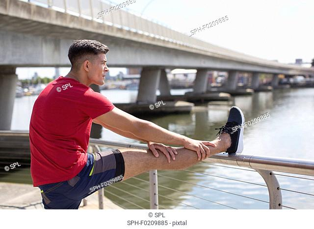 Young man stretching leg on railing before a run