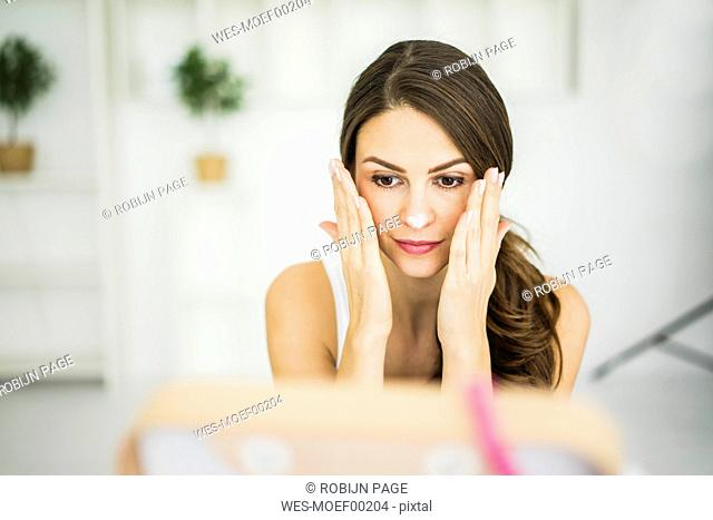 Portrait of woman creaming her face