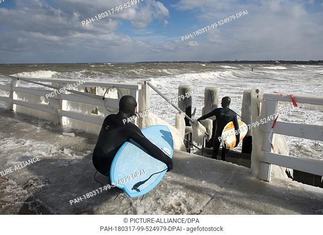 17 March 2018, Germany, Timmendorfer Strand: Two sufers in thick neoprene suits wait for the right wave at the Baltic Sea. Photo: Rainer Jensen/dpa