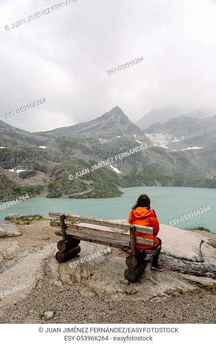 Young woman sitting on bench at Alpine lake with space for copy. She is curly and wears casual clothes. Rear view