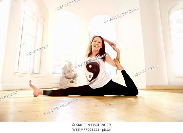 Woman in sunny yoga studio getting into Parivrrta Janu Sisasana pose