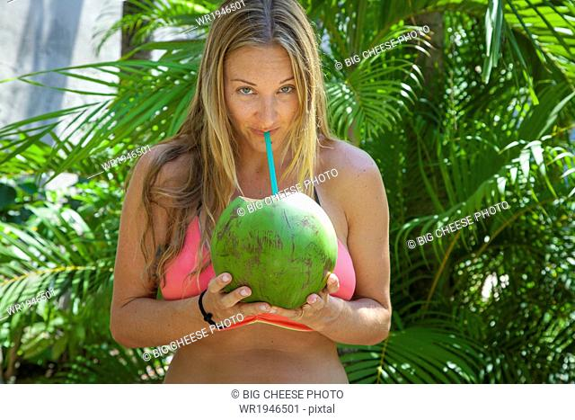 Young woman in a bikini drinking from a coconut