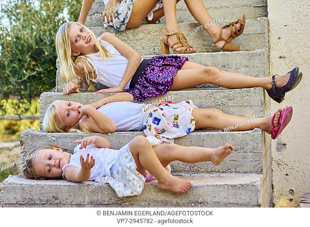 young infant girls laying on stairs outside in garden. Australian ethnicity. During holiday stay in Hersonissos, Crete, Greece