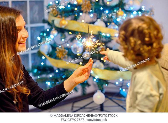 Teen girl holding sparklers and children