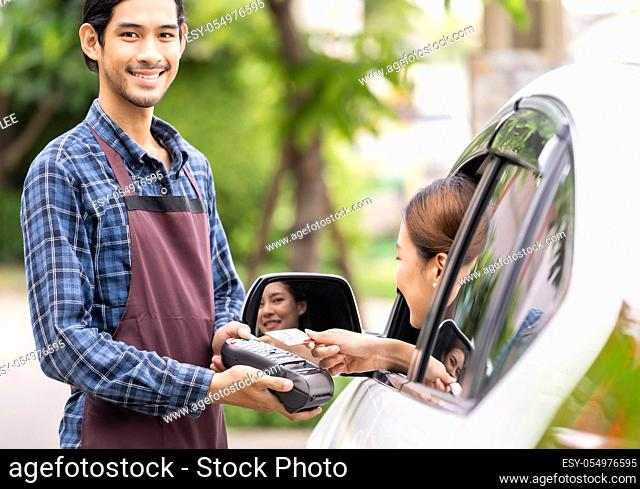 Portrait of asian restaurant employer hold credit card reader for asian woman customer to make mobile payment contactless technology on drive thru food service...