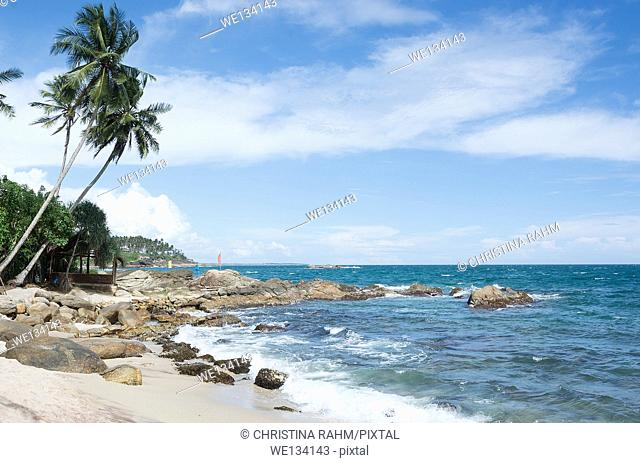 Tropical rocky beach with coconut palm trees, sandy beach and ocean. Tangalle, Southern Province, Sri Lanka, Asia
