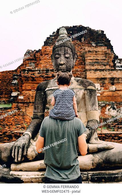 Thailand, Ayutthaya, Father and daughter looking at a Buddha statue at Wat Mahathat