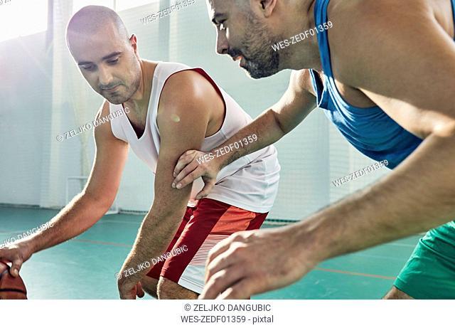 Men playing basketball, defence
