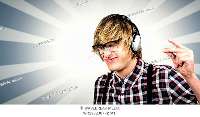 Male hipster using headphones over abstract background