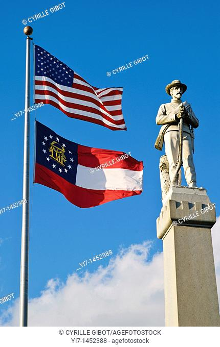 Georgia State and United States flags next to the Confederate Soldier Monument in Moultrie, Georgia, USA. A confederate soldier monument stands on the...