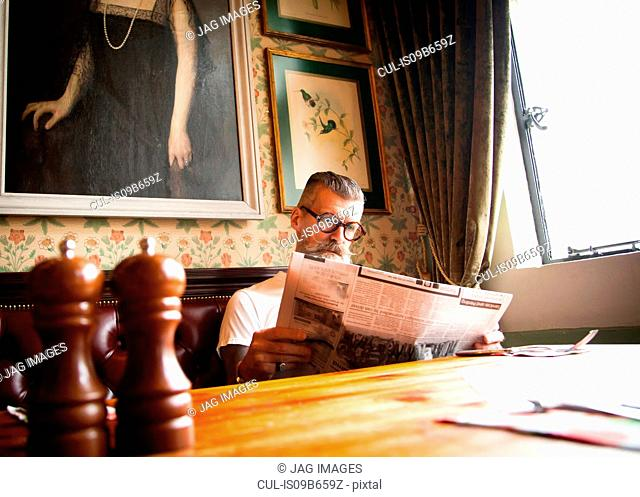 Quirky man reading newspapers in bar and restaurant, Bournemouth, England