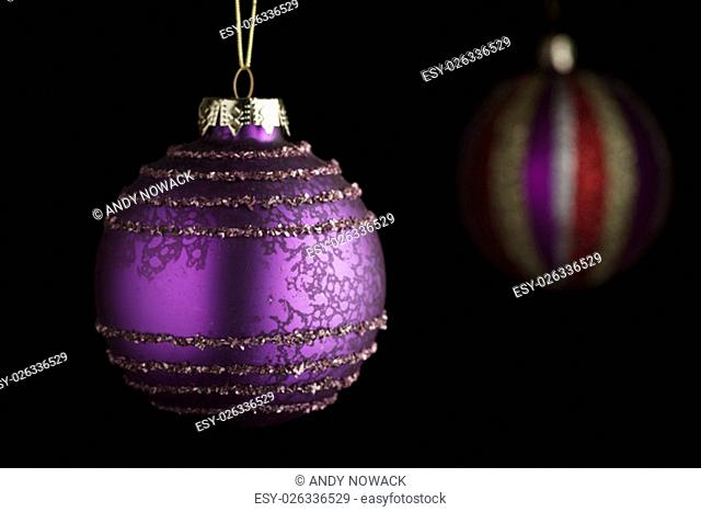violet christmas ball in the foreground with vertically striped christmas ball in blurry background in sidelight before black