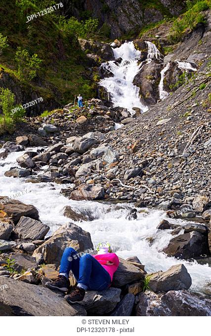 A woman taking a break from sea kayaking in Kenai Fjords National Park relaxes by a rushing stream while her partner explores a waterfall; Alaska