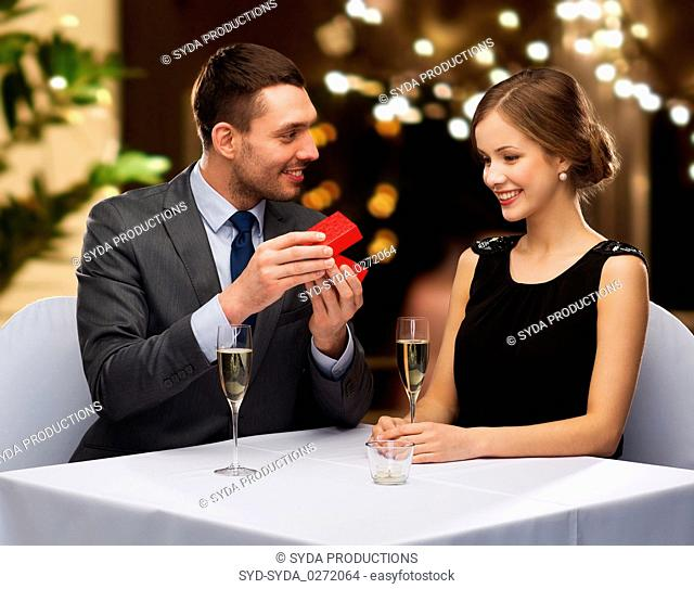 man showing woman present in red box at restaurant