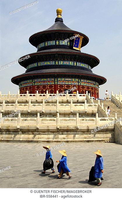 Three female sanitation workers walking past the Hall of Prayer for Good Harvest, Temple of Heaven, Beijing, China
