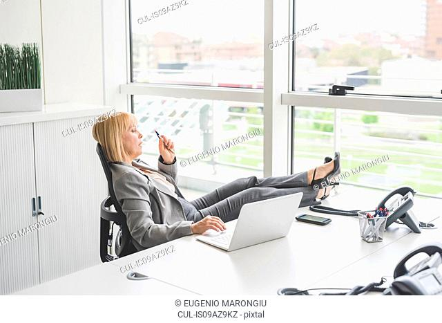 Mature businesswoman with feet up on office desk