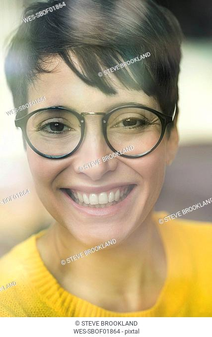 Portrait of laughing woman behind windowpane