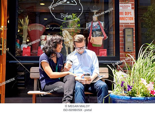 Couple sitting on bench, outside bakery, holding coffee cups