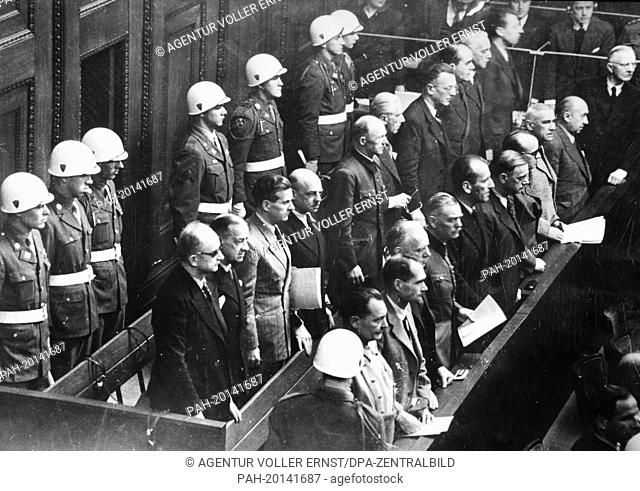The main defendants as war criminals of the Nazi regime are surrounded by military policemen at the Nuremberg Trials in 1946 in front of the International...