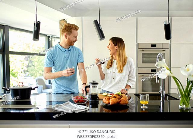 Couple standing in kitchen, preparing healthy breakfast, chopping fruits