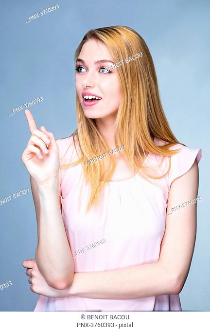 Portrait of a smiling young woman raised finger on the side