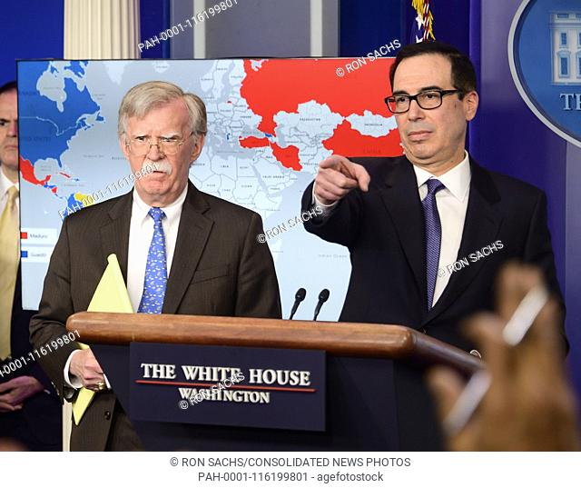 United States Secretary of the Treasury Steven T. Mnunchin, right, conducts a briefing with National Security Advisor John R