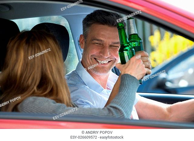 Close-up Of Happy Mature Couple Sitting Inside The Car Enjoying Beer