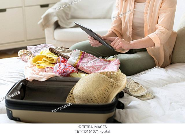 Woman using digital tablet while packing suitcase