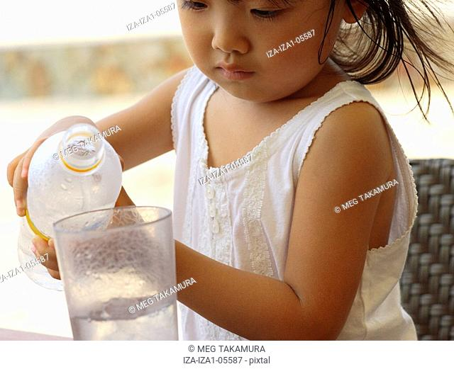 Close-up of a girl pouring water from a water bottle in a glass