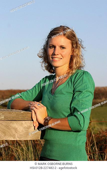 Young blonde woman outdoors leaning on a fence