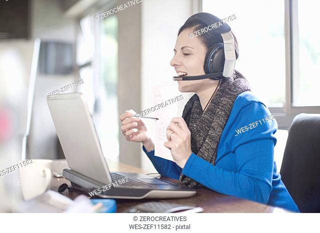 Smiling woman at desk with laptop and headset