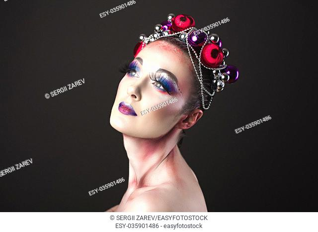Elegant model with bright New Year's Eve make-up in a wreath of Christmas toys. Studio shot