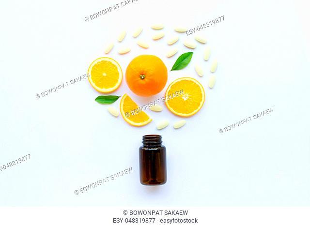 Vitamin C bottle and pills with orange fruit on white background