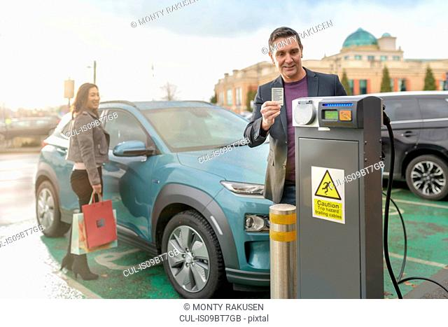 Man and woman charging electric car at car charging park, Manchester, UK