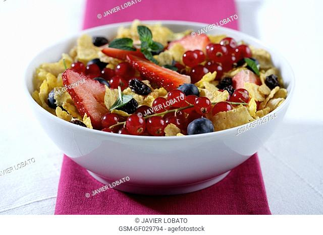 Bowl with corn flakes, large strawberries, recurrants, raisins and blueberries