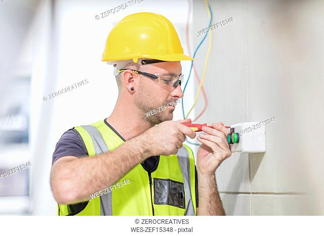 Electrician screwing in wire on construction site