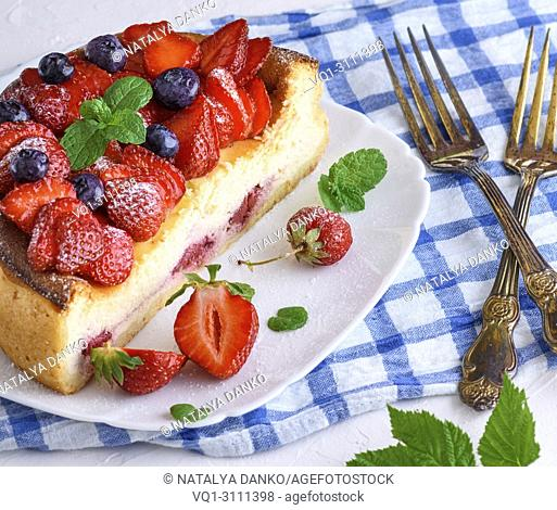 cheesecake made of cottage cheese and fresh strawberries on a white ceramic plate, close up