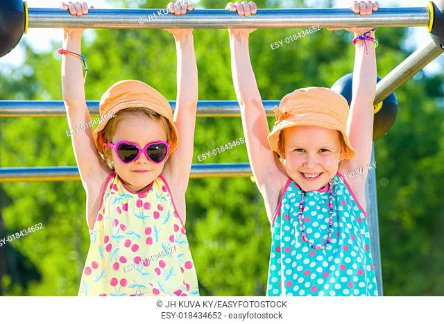 Two young girls on the jungle gym, sunny day