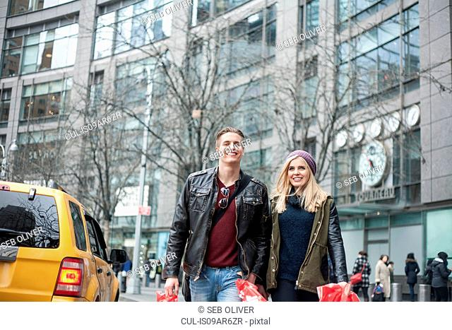 Young couple strolling with shopping bags on street, New York, USA