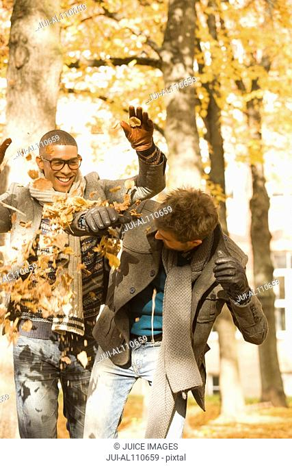 Young university friends throwing autumn leaves on college campus