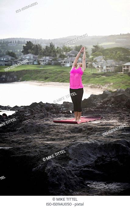 Woman at coast practicing yoga with arms raised, Hawea Point, Maui, Hawaii, USA
