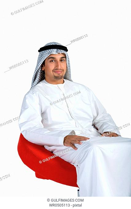 Young man sitting on chair, smiling, portrait
