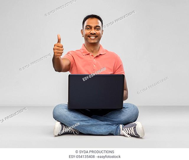 happy indian man with laptop showing thumbs up